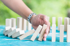 Lösungskonzept mit der Hand, die Holzklötze vom Fallen stoppt stockbilder