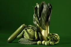 Lövrika grönsaker mot grön bakgrund Fotografering för Bildbyråer