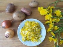 Löwenzahnblumen mit Kartoffeln und Zwiebelburgern Lizenzfreie Stockbilder