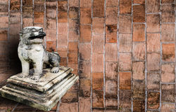 Löwestatue und alte Backsteinmauer. Stockfoto
