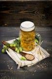 Lúpulos e sementes do malte e jarro dos pontos completamente com cerveja no guardanapo de pano Imagens de Stock Royalty Free