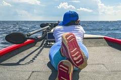 Lüge der jungen Frau auf Fischerboot mit Fischsucher, echolot, Sonar an Bord stockfotos