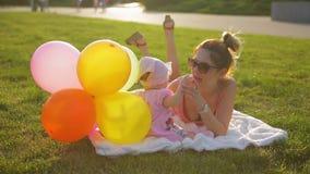 Lüge der jungen Mutter und der Säuglingstochter auf der weißen Decke gelegt auf Gras im Park und Spiel mit Ballonen gegen Glanz d stock video footage