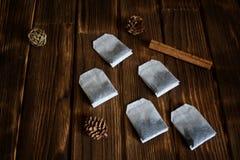 Lüge mit fünf Teebeuteln auf einer Holzoberfläche mit Zimt stockfotografie