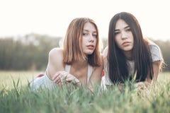 Lüge mit zwei jungen Frauen auf dem iawn Stockfotografie