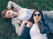 Lüge mit zwei Mädchen auf Gras Stockfotos