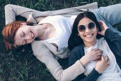 Lüge mit zwei Mädchen auf Gras Lizenzfreie Stockfotos