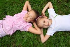 Lüge mit zwei Mädchen auf Gras mit geschlossenen Augen Lizenzfreies Stockfoto