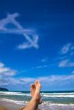 Lügen auf dem Strand mit Dollarsymbol Stockbilder