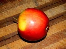 Lügen auf einem frischen roten Apfel des hölzernen Brettes Lizenzfreie Stockfotos