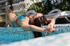 Lügenc$ein sonnenbad nehmen der Frau am Rand eines Pools Stockfoto