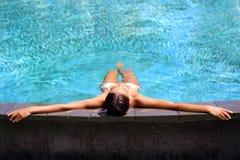 Lügenentspannung der Bikinifrau im Unendlichkeitspool lizenzfreie stockfotos