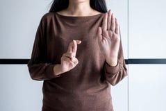 Lügenfrau mit Lügner erklärenden und betrügenden den Handkreuzungsfingern, Konzept der Aprilscherze Tages, Stoppschild stockfotos