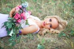 Lügenmädchen mit einem Blumenstrauß Stockfotos