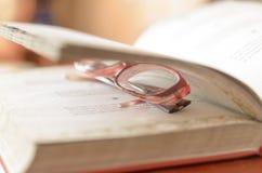 Lügenoffenes buch und Gläser Stockfotos