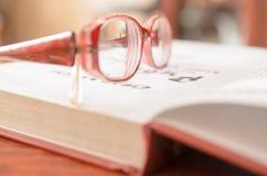 Lügenoffenes buch und Gläser Lizenzfreie Stockfotos