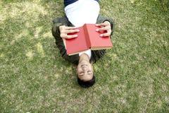 Lügenrotes Buch des Jungen leseauf grünem Gras stockfotografie