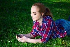 Lügenund hörende Musik der Jugendlichen mit intelligentem Telefon im Park Lizenzfreies Stockfoto