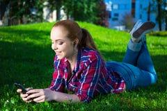 Lügenund hörende Musik der lächelnden Jugendlichen mit intelligentem Telefon Lizenzfreies Stockfoto