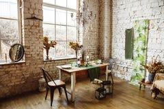 Lüpfen Sie Innenraum mit Backsteinmauer, Tabelle und Stühlen Stockfotos