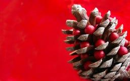L'†de temps de Noël «a décoré le cône de pin avec le fond rouge Images libres de droits