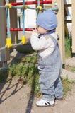 L'âge de bébé de 11 mois joue sur le terrain de jeu dehors Image libre de droits