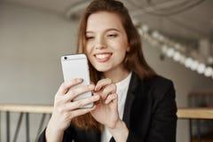 L'âge de la technologie monte Portrait de fille à la mode avec du charme en café, souriant tout en passant en revue dans l'Intern Image stock