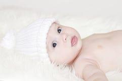 L'âge de sourire de bébé de 4 mois dans le blanc a tricoté le chapeau Photo stock