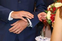 l'échange sonne le mariage La jeune mariée place l'anneau sur la main du ` s de marié Images stock