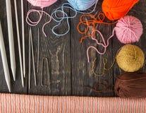 L'écharpe, les aiguilles de tricotage et les crochets de crochet tricotés chauds, écheveaux bavardent sur les conseils foncés image libre de droits