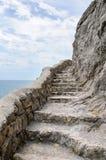 L'échelle en pierre a coupé de la roche au-dessus de la mer Image stock