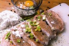 L'échine de porc crue coupe sur une planche à découper avec des herbes, romarin, thym, piment, le sel, poivre sur la planche à dé photos stock