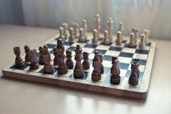 L'échiquier matériel en bois de rétro style avec des pièces d'échecs a placé prêt pour le jeu d'esprit stratégique image stock