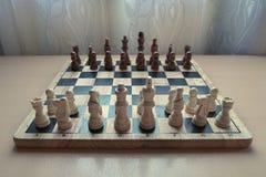 L'échiquier matériel en bois de rétro style avec des pièces d'échecs a placé prêt pour le jeu d'esprit stratégique photo libre de droits