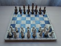 L'échiquier matériel en bois de rétro style avec des pièces d'échecs a placé prêt pour le jeu d'esprit stratégique images libres de droits