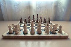 L'échiquier matériel en bois de rétro style avec des pièces d'échecs a placé prêt pour le jeu d'esprit stratégique photographie stock libre de droits