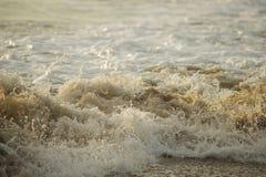 L'éclaboussement ondule sur une plage tropicale pendant le coucher du soleil Beau éclabousse des vagues de mer Image stock