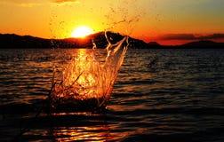 L'éclaboussure de l'eau sous le coucher de soleil Photographie stock libre de droits
