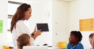 L'école de enseignement de professeur badine sur le comprimé numérique dans la salle de classe clips vidéos