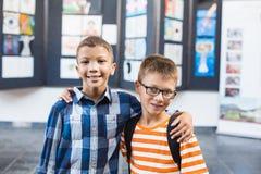 L'école de sourire badine la position avec le bras autour dans la salle de classe Image libre de droits
