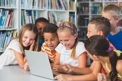L'école de sourire badine regarder l'ordinateur portable dans la bibliothèque Images libres de droits