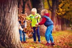 L'école heureuse avec plaisir badine, des amis ayant l'amusement jetant les feuilles tombées dans le parc d'automne Photo libre de droits