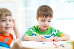 L'école maternelle badine des garçons dessinant à la crèche Photographie stock libre de droits