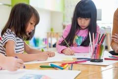 L'école maternelle badine le dessin avec le crayon de couleur sur le livre blanc sur la table Photos stock