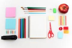 L'école a placé avec des carnets, des crayons, la brosse, des ciseaux et la pomme sur le fond blanc Photographie stock libre de droits
