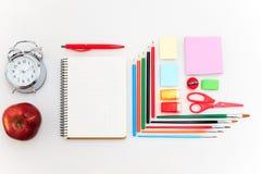 L'école a placé avec des carnets, des crayons, la brosse, des ciseaux et la pomme sur le fond blanc Image libre de droits