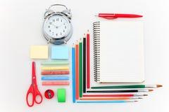 L'école a placé avec des carnets, des crayons, la brosse, des ciseaux et la pomme sur le fond blanc Photo stock