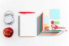 L'école a placé avec des carnets, des crayons, la brosse, des ciseaux et la pomme sur le fond blanc Images stock