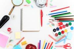 L'école a placé avec des carnets, des crayons, la brosse, des ciseaux et la pomme sur le fond blanc Photographie stock