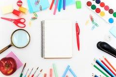 L'école a placé avec des carnets, des crayons, la brosse, des ciseaux et la pomme sur le fond blanc Image stock